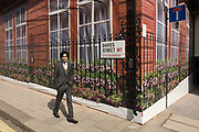 An ungainly young man walks past the construction hoarding belonging to Claridges in Mayfair, Westminster. He walks and looks in the viewer's direction with a confused and awkward expression. We see the street sign for Davies Street, W1 in the borough of Westminster. The sign is genuine but the railings, flowers and red brickwork are all fake - printed on to the temporary hoarding.