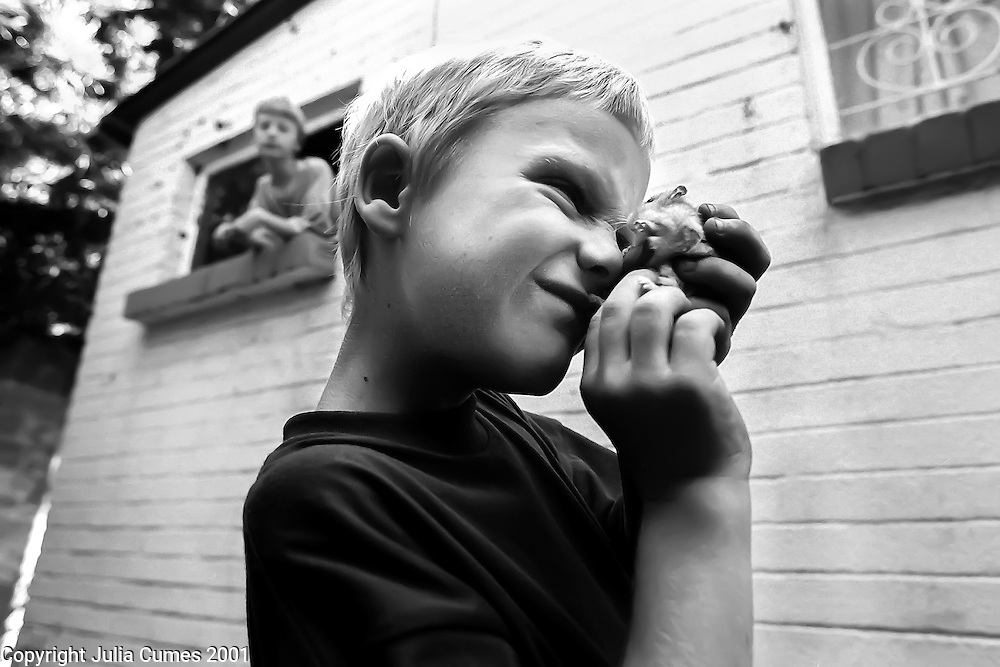 Matthew Blackburn plays with his hamster outside his home in Sandringham, South Africa.  Looking out the window behind him is his older brother, Stuart.  Matthew lives with his parents and two brothers in a predominantly white suburb of Johannesburg.  Matthew's mother, Trish, is an assistant accountant and his father, Chris, is a retauranteur currently between jobs.  The Blackburn boys attend the same government school their mother attended as a child except that the school is now predominantly black rather than all-white.  Because of the racial mix of the school, most of Matthew's friends are black.  ?Our kids are growing up in a totally different South Africa,? says Chris Blackburn.