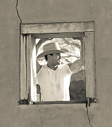 cowboy standing in a broken down window frame on a ranch in New Mexico