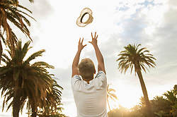 Teenager boy throwing hat in air palm trees happy