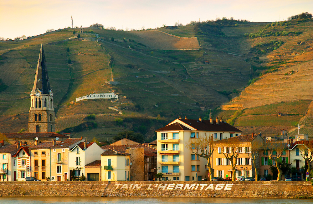 The Church, the name of the town painted in large white letters and a sign with Ermitage Chapoutier. The Hermitage vineyards on the hill behind the city Tain-l'Hermitage, on the steep sloping hill, stone terraced. Sometimes spelled Ermitage. Tain l'Hermitage, Drome, Drôme, France, Europe