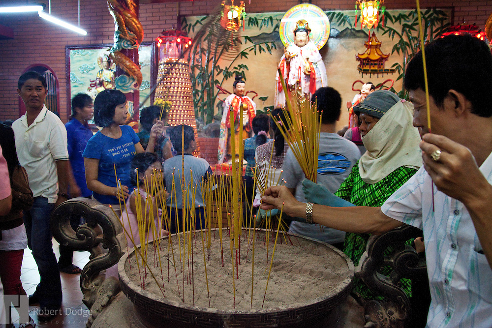 Residents of Chinatown in Ho Chi Minh City light incense and pray at the Thien Hau temple. Thien Hauis a deity of traditional religion in China. She is worshipped in the maritime provinces of China, in overseas Chinese communities and Southeast Asia. Robert Dodge, a Washington DC photographer and writer, has been working on his Vietnam 40 Years Later project since 2005. The project has taken him throughout Vietnam, including Hanoi, Ho Chi Minh City (Saigon), Nha Trang, Mue Nie, Phan Thiet, the Mekong, Sapa, Ninh Binh and the Perfume Pagoda. His images capture scenes and people from women in conical hats planting rice along the Red River in the north to men and women working in the floating markets on the Mekong River and its tributaries. Robert's project also captures the traditions of ancient Asia in the rural markets, Buddhist Monasteries and the celebrations around Tet, the Lunar New Year. Also to be found are images of the emerging modern Vietnam, such as young people eating and drinking and embracing the fashions and music of the West. His book. Vietnam 40 Years Later, was published March 2014 by Damiani Editore of Italy.