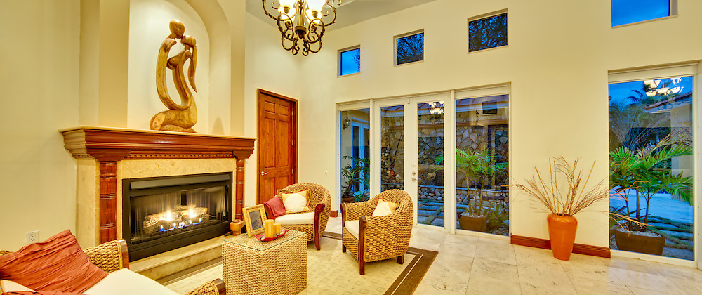 View of large living room with fireplace and large windows with outside view of patio.