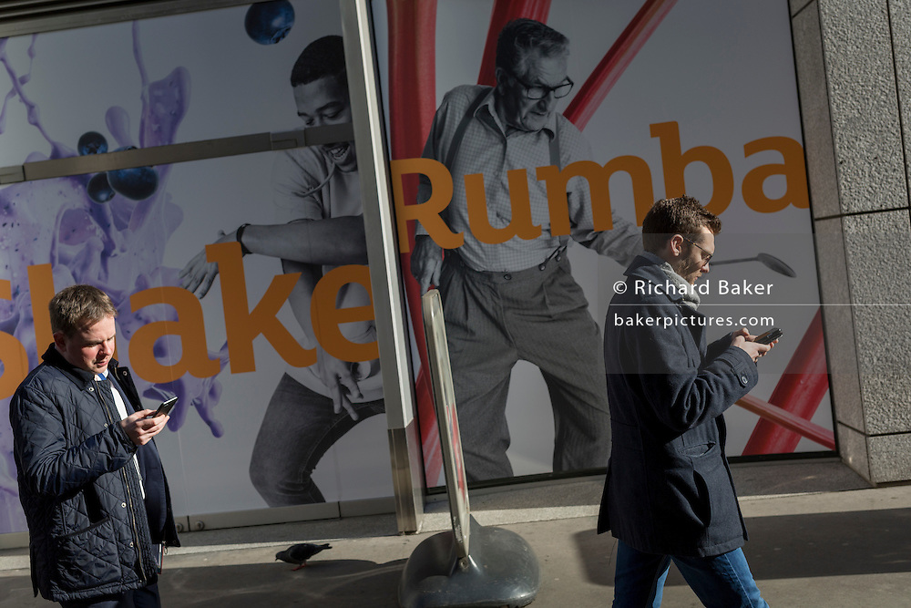 Two men walk and check social media, in front of a Sainsbury's poster, on 13th February 2017, in the City of London, United Kingdom.