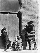 Three beggars, a man, woman, and child in front of convent doors. photographic print : albumen. [between 1860 and 1880] Mexico