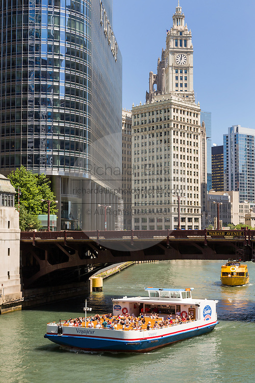 A sightseeing boat along the Chicago River looking toward the Wabash Bridge, Wrigley Building and skyline during summer in Chicago, Illinois, USA