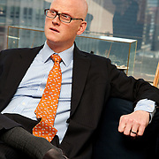 Bald Man with glasses dressed in suit and tie listens to someone in office with Manhattan NYC daytime skyline visible through window behind him
