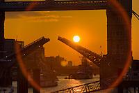 sun sets behind an open tower bridge bascules