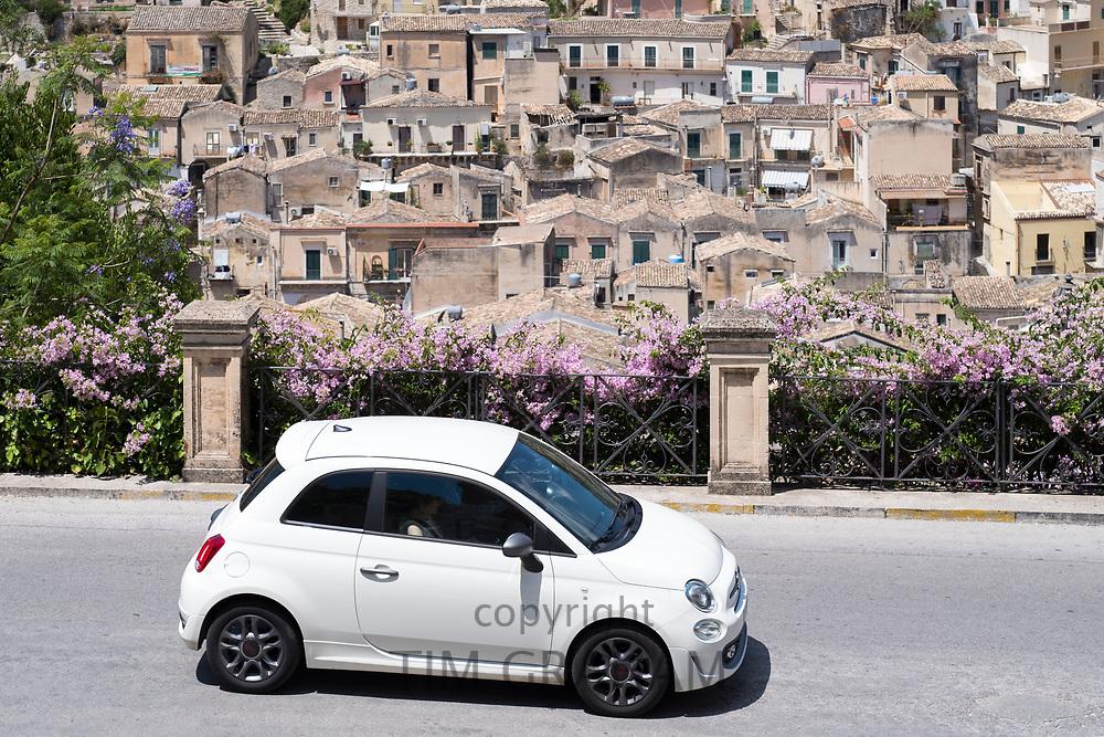 White colour Fiat 500 Cinquecento in hill city of Modica Alta looking towards Modica Bassa, Sicily, Italy