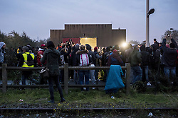 October 24, 2016 - Calais, France - surrounded by journalists, refugees waiting outside the hangar distribution of refugees in Calais, France on october 24, 2016. The dismantling of the jungle began Monday morning. Refugees come accompanied by the associations to the starting center ''C.A.O.''. Police frames the device. More than 850 press credentials were distributed. (Credit Image: © Julien Pitinome/NurPhoto via ZUMA Press)