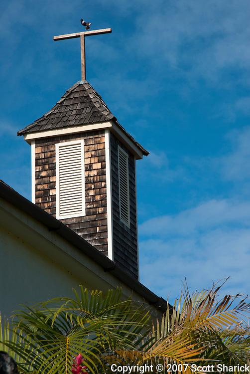 A bird lands on the broken cross on top of a church steeple in Hawaii.
