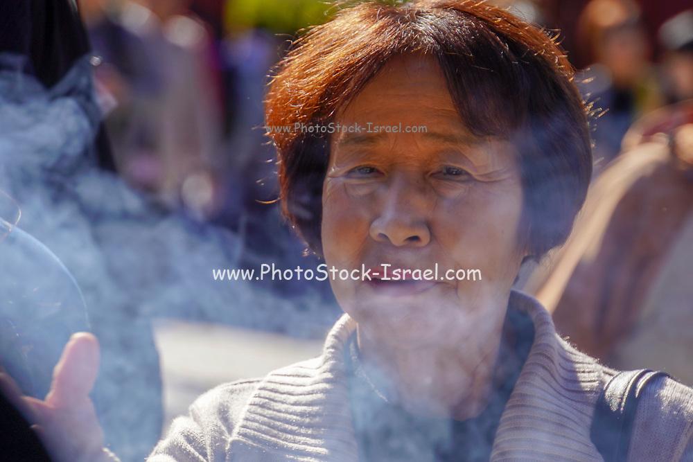 Japan, Tokyo, Asakusa, Senso-ji temple woman burning incense sticks