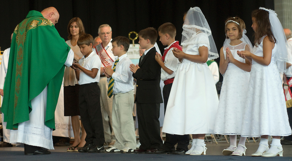 Italian Archbishop Claudio Maria Celli begins communion with several first communicants, Sunday, July 18.