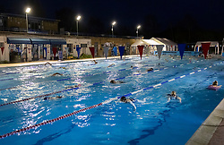 © Licensed to London News Pictures. 29/03/2021. London, UK. Swimmers exercise at Hampton outdoor pool in south west London before dawn. The pool opened for the return to outdoor swimming at 4:45am. Covid regulations have changed today to allow gatherings up to six people outdoors. With sporting facilities, such as tennis,basketball courts and outdoor swimming pools allowed to reopen. Photo credit: Peter Macdiarmid/LNP