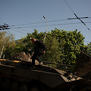 A pro-Russia activist climbs up a military tank, set alight hours after deadly clashes between separatists armed groups and the Ukrainian Army over the control of key buildings in the city.