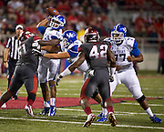 Kentucky Wildcats  offensive linemen Zach West (75) and Darrian Miller (77) block as quarterback Morgan Newton (12) makes a pass over Arkansas Razorbacks defensive tackle Alfred Davis (51) and defensive end Chris Smith (42) looks on as during the first half of a game at Donald W. Reynolds Razorback Stadium in Fayetteville, Ark., on Oct.. 13, 2012. Photo by Beth Hall