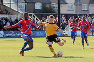 Newport's Mark Byrne takes a shot against Dagenham's Ian Gayle. Skybet football league two match , Newport county v Dagenham & Redbridge at Rodney Parade in Newport, South Wales on Saturday 18th April 2015.<br /> pic by David Richards, Andrew Orchard sports photography.