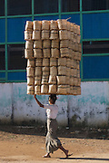 Woman carries two hundred baskets on her head to market, Pathein
