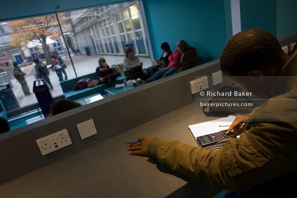 Young man studies at workstation in communal area at London Metropilitan University's Holloway Road campus.