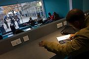 Young man studies at workstation in communal area at London Metropilitan University's Holloway Road campus.