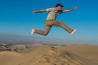 man jumping in the desert in the peruvian coast at Ica Peru