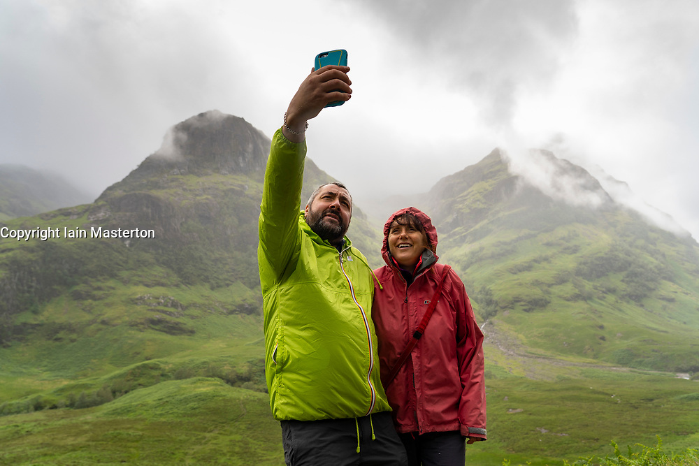Glen Coe, Scotland, UK. 4 July, 2020. Tourists travel to Glen Coe on first weekend after 5 mile travel restriction was lifted by the Scottish Government. Pictured; couple take selfie photograph with spectacular mountain backdrop in Glen Coe.  Iain Masterton/Alamy Live News