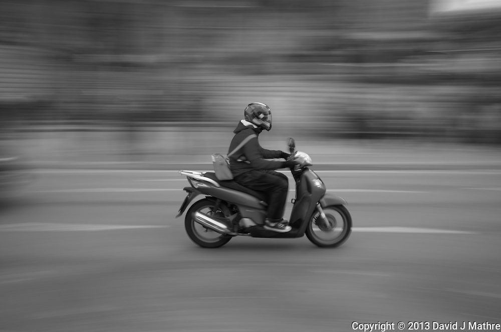 Motorcycle Passing the Sagrada Familia Cathedral in Barcelona, Spain. Image taken with a Leica X2 camera (ISO 100, 24 mm, f/16, 1/15 sec). In camera B&W.