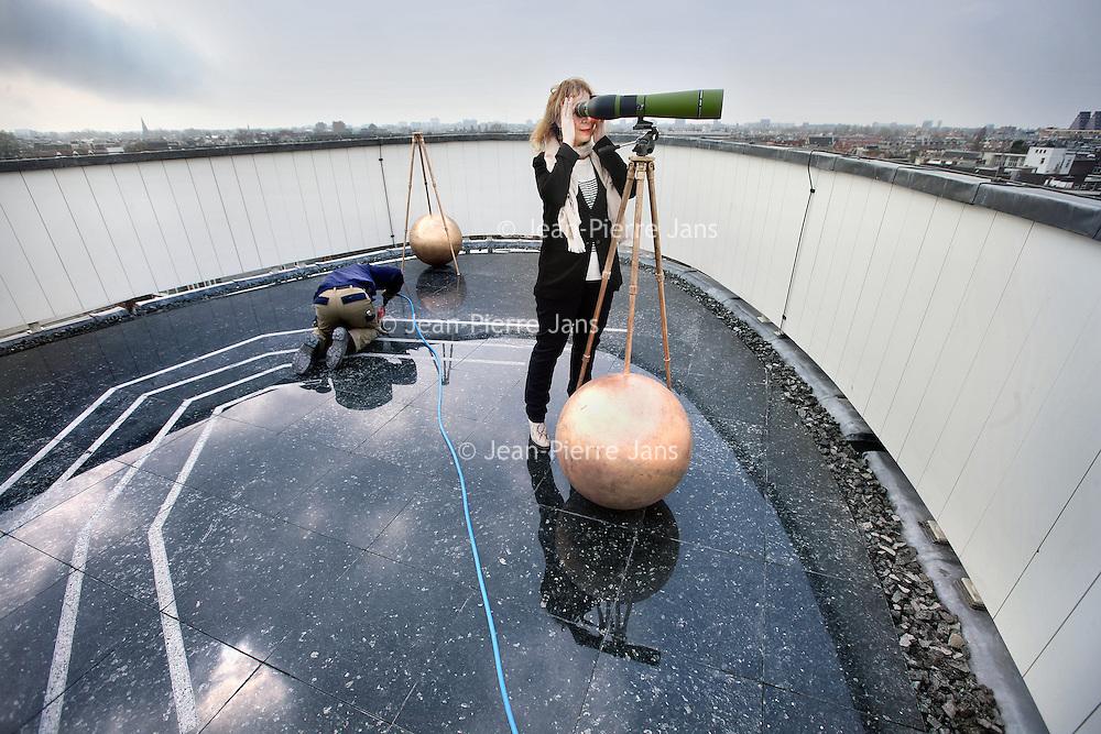 Nederland, Amsterdam , 17 april 2013.<br /> Het z.g. Observatorium op het dakterras van Felix Meritis aan de Keizersgracht.<br /> Het Observatorium, de Sterrenschouwplaats, van Felix Meritis is de plek waar ooit de Felixianen de hemellichamen bestudeerden en waar Arthur Schopenhauer genoot van het weidse uitzicht over de stad. <br /> Hier richtte men overdag de kijkers op de bebouwde omgeving en 's nachts op de sterrenhemel. Het Observatorium is het oudste nog bestaande astronomisch Observatorium in Nederland dat ontworpen is met de nadrukkelijke bedoeling er wetenschappelijk verantwoorde sterrenkundige en meteorologische waarnemingen te verrichten.<br /> Kunstenaar/filosoof Joseph Semah zal het laatste deel van zijn driedelig kunstwerk in Felix Meritis met de installatie op het Observatorium afronden.<br /> Op het Observatorium wordt een marmeren vloer aangebracht met daarop weergegeven de sterrenhemel vervlochten met de grachten. Hierop worden vier bijzonder vormgegeven kijkers geplaatst waarmee heel Amsterdam te bekijken is. De kijkers zullen niet, zoals in het verleden, gericht zijn op de sterren maar op teksten en citaten, die op een aantal markante historische en moderne gebouwen geplaatst zijn. Zo worden gebouwen en citaten met elkaar verbonden en wordt ook de oude en nieuwe geschiedenis van de stad verbonden. <br /> Op de foto: directrice Linda Bouws bekijkt de stad door de verrekijker die is opgesteld bij het Observatorium waar de laatste werkzaamheden worden verricht aan de granieten vloer.<br /> Foto:Jean-Pierre Jans