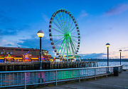 "The Seattle Great Wheel is a giant Ferris wheel at Pier 57 on Elliott Bay in Seattle, Washington, United States. With an overall height of 175 feet, it became the tallest Ferris wheel on the west coast of the United States when it opened on June 29, 2012. Seattle was the third city in North America to offer a wheel of this design, following the Niagara SkyWheel at Clifton Hill, Niagara Falls, Canada, which is also 175 feet tall, and the larger Myrtle Beach SkyWheel in South Carolina, which is 187 feet tall. The Seattle wheel is the only one of the three to be built over water. The Seattle Great Wheel has 42 climate-controlled gondolas, each able to carry up to eight passengers (except the ""VIP"" gondola, seating four), giving a maximum capacity of over 300. The 12-minute ride extends 40 feet out over Elliott Bay. Seattle businessman and waterfront developer Hal Griffith has envisioned a Ferris wheel on Elliott Bay for nearly 30 years. Along with his family, he is the owner of the Pier 57 upon which the Seattle Great Wheel is located. In addition to the wheel, the pier is the location of Miner's Landing, which consists of souvenir gift shops, tourist attractions, and variety of seafood restaurants. During the 1980s, Griffith began developing plans to ensure the perpetual existence and success of the family's business ventures on the pier. His plans had long included continual development of the waterfront on Puget Sound to provide entertainment and recreational opportunities for tourists and local residents. His goal was to drive success through innovative ideas, staying a step ahead of the competition. Griffith often met logistical and political roadblocks that inhibited development on the waterfront, but he was determined to build the Ferris wheel on Pier 57, located adjacent to the Alaskan Way Viaduct."