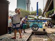25 JANUARY 2015 - BANGKOK, THAILAND: A street food vendor (left) talks to her neighbor while her husband prepares their cart before starting work. After months of relative calm following the May 2014 coup, tensions are increasing in Bangkok. The military backed junta has threatened to crack down on anyone who opposes the government. Relations with the United States have deteriorated after Daniel Russel, the US Assistant Secretary of State for Asian and Pacific Affairs, said that normalization of relations between Thailand and the US would depend on the restoration of a credible democratically elected government in Thailand.    PHOTO BY JACK KURTZ