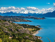 See the Northern Patagonian Ice Field across General Carrera Lake, northeast of Puerto Guadal, Chile, South America. The glacially carved lake is surrounded by the Andes mountain range and drains to the Pacific Ocean on the west through the Baker River. The coast of the lake was first inhabited by criollos and European immigrants between 1900 and 1925. In 1971 and 1991, eruptions of the Hudson Volcano severely affected the local economy, especially that of sheep farming.