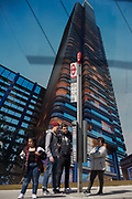 travellers wait for a bus under a construction hoarding showing the Foster-designed Principal Tower thats under construction on Shoreditch High Street, on 10th May 2017, in London, England.