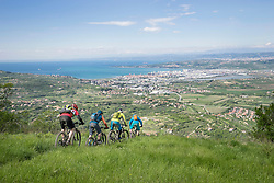 Mountain bikers moving downhill with cityscape and sea in foreground