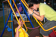 two female children of 13 playing on a swing in a playground
