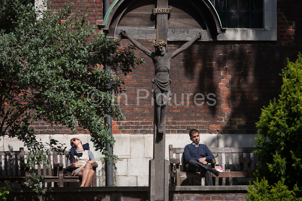 Lunchtime Londoners rest in summer sunshine beneath a crucifix, 15th August 2016 in the City of London, UK. Siting on benches outside the church of St Andrew-by-the-Wardrobe on Queen Victoria Street. As the effigy of jesus seemingly looks down at her, the lady is asleep with head tilted at an awkward angle, a man sits with the remains of his lunch by his side. First mentioned around 1170, the church got its name when in 1361, Edward III moved his Royal Wardrobe to just north of the church. It was from this association that the church acquired its unique name. It was lost in the Great Fire of London in 1666 then rebuilt in 1695 and destroyed again by German bombing during WW2. when only the tower and walls survived. It was rebuilt and rededicated in 1961.