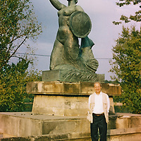1. When was this photo taken?<br /> <br /> August 2003<br /> <br /> 2. Where was this photo taken?<br /> <br /> Poland<br /> <br /> 3. Who took this photo?<br /> <br /> Patricia Zuroski<br /> <br /> 4. What are we looking at here?<br /> <br /> My husband, Gregory, and I planned a trip to Poland in 2003 to visit Warsaw, Krakow and the small town that his grandfather came from, Sierpc. I don't remember where this was taken, but probably Warsaw. Gregory passed away in 2013 and I asubmit this photo in his memory.<br /> <br /> 5. How does this old photo make you feel? <br /> <br /> It seems so recent. I love that Gregory has his travel vest on. He has a map or pamphlet in his pocket. He needed all the pockets for all the things he collected along the way.<br /> <br /> 6. Is this what you expected to see?<br /> <br /> I didn't realize that I had lost a roll from our Poland trip. It was a nice surprise.<br /> <br /> 7. What kind of memories does this photo bring back?<br /> <br /> I had never had an image of Poland and this was a trip with many good memories.<br /> <br /> 8. How do you think others will respond to this photo? <br /> <br /> I hope it makes people happy to see someone who loved to travel and loved seeking family history.
