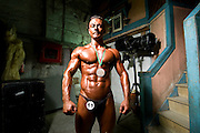 For two years in a row, in a rundown theater in Porto, the Portuguese National Championship of Bodybuilding WABBA happened. Several athletes, from allover the country came to this one day competition. <br /> These are photos from the backstage, where the athletes exercise and get body paint for the stage presentation. The muscles and the gold and brown colors get ready in the confusion of tubes, abandoned wood from different theater plays, photos from the past and dressing rooms with 100 years old.  Ricardo Oliveira, second place in his category.