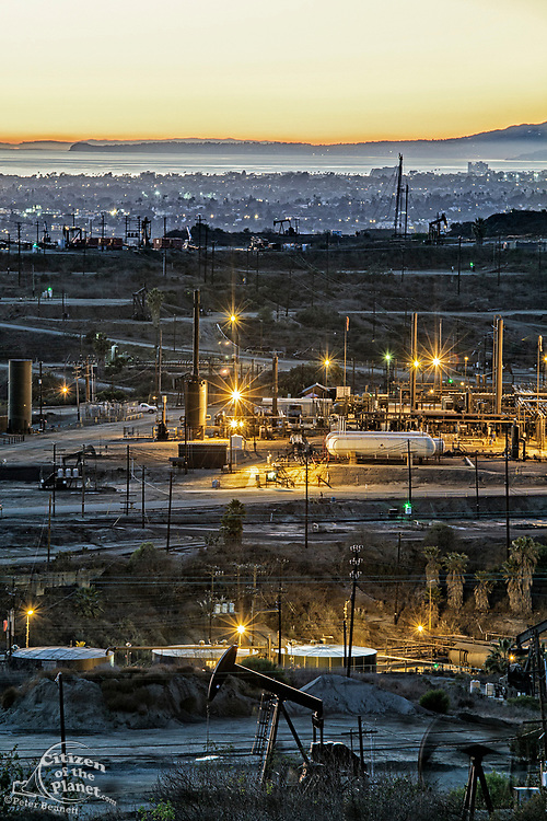 Inglewood Oil Field, one of the largest urban oil fields in the country, with city of Santa Monica and Malibu coastline in the background. Fracking on the field continues to spark conroversey for the over one million residents who live within 5 miles of the oil field. Baldwin Hill, Los Angeles,, California, USA