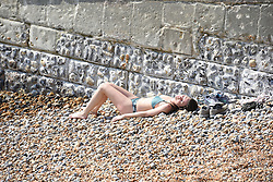 © Licensed to London News Pictures. 11/04/2020. Brighton, UK. A woman sunbathing on Hove beach at Brighton and Hove, during a pandemic outbreak of the Coronavirus COVID-19 disease.  Photo credit: Liz Pearce/LNP