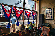 Top Cigars owner Crist Mena stands outside his Cigar Club as he looks forward to customers returning as non-essential businesses are allowed to open along Calle Ocho in Little Havana on Tuesday, May 19, 2020.