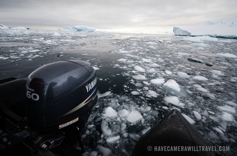 The outboard motor on the back of a zodiac inflateable plows through the brash ice floating on top of the water in Curtis Bay, Antarctica.