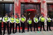 Police at an Extinction Rebellion protest line up in a row outside Guildhall, which has been covered in red paint to signify blood, on 27th August, 2021 in London, United Kingdom. The activist group Extinction Rebellion XR are planning actions of disruption for two weeks straight beginning on August 23rd, 2021 in an effort to bring awareness and priority to the global climate emergency in advance of the COP 26 Summit which will be held in Glasgow later this year.
