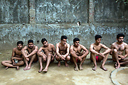 Indian Khusti wrestlers wait to fight at a wrestling Akhara in New Delhi, India.<br /> Pehlwani, or kusti is a form of wrestling from South Asia. It was developed in the Mughal Empire by combining native malla-yuddha with influences from Persian koshti pahlavani. A practitioner of this sport is referred to as a pehlwan.