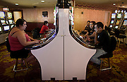 Travelers try their luck, gambling at a slot machine in a casino in Las Vegas.