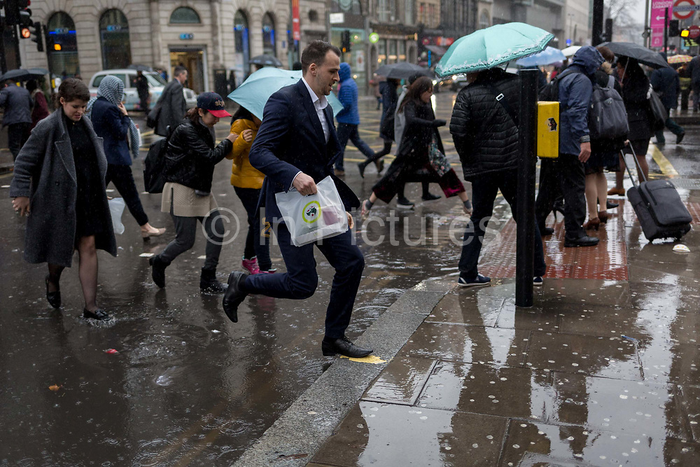 Storm Georgina swept across parts of Britain and in central London, lunchtime office workers were caught out by torrential rain and high winds, on 24th January 2018, in London, England. Pedestrians resorted to leaping across deep puddles at the junction of New Oxford Street and Kingsway at Holborn, the result of overflowing drains. First in a sequence of two photos.