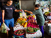 """14 FEBRUARY 2019 - SIHANOUKVILLE, CAMBODIA: A Chinese worker buys vegetables from a Cambodian market vender in the Leu Market in Sihanoukville. There are about 80 Chinese casinos and resort hotels open in Sihanoukville and dozens more under construction. The casinos are changing the city, once a sleepy port on Southeast Asia's """"backpacker trail"""" into a booming city. The change is coming with a cost though. Many Cambodian residents of Sihanoukville  have lost their homes to make way for the casinos and the jobs are going to Chinese workers, brought in to build casinos and work in the casinos.      PHOTO BY JACK KURTZ"""