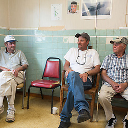 "August 4, 2017 - Tangier Island, VA - <br /> Inside the ""Situation Room,""  (named after a small briefing room in the White House) is a small room inside the former Tangier Island health clinic, where watermen gather at the end of the day to ""solve all the world's problems,"" according to Tangier Island Mayor James ""Ooker"" Eskridge (center).  Richard Pruitt, left, and Danny McCready, right, flank the mayor on either side.  Photo by Susana Raab/Institute"