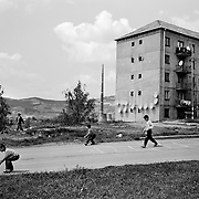 Children play in a housing estate surrounded by communist style housing blocks in the heart of a housing estate in the small Romanian town of Copsa Mica,  Transylvania, Romania. Copsa Mica was once described as the most polluted town in Europe. May 9, 2008. Photo Tim Clayton....Copsa Mica, a small industrial town deep in Transylvania, Romania, was described during the 1990s as the most polluted town in Europe with lead levels reaching were more than 1000 times the allowable International limits and life expectancy nine years shorter than the National average...The pollution was caused entirely by two factories, Carbosin produced black for dies and tires and closed in 1993 while Sometra, a nonferrous smelter is still operational today...The pollution was so bad sheep were black, covered in soot and health officials advised against eating livestock or vegetables and drinking the water or milk...The Communist rule of Nicolae Ceausescu is blamed for the widespread environmental degradation that left industrial parts of Romania in ecological disaster. Industry was situated in a way to concentrate pollution in small areas leaving the rest of the country relatively free of pollution.Copsa Mica in particular was left an environmental disaster...The pollution caused a direct affect on human health with widespread Lung disease, Impotency, the highest infant mortality rate in Europe, Lead poisoning andbehavioral problems...Fifteen years on since the closure of Carbosin in 1993, the factory skeleton remains as part of the towns bleak landscape, Unfinished communist style housing blocks still stand in the heart of the towns housing estate. The town's inhabitants arestill trying to recover from the long lasting effects of pollution...Recent survey's found the soil contained so much lead that it was 92 times above the permitted level; the vegetation had a lead content 22 times above the permitted level. While toxins have penetrated at least one meter (three fe