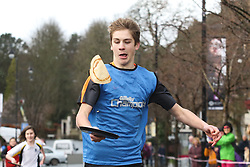 © Licensed to London News Pictures. 09/02/2016. Ilkley, UK. A competitor in this year's pancake race in Ilkley, West Yorkshire, flips his pancake in the dash towards the finish line. The race is held annually in the Yorkshire town of Ilkley on Shrove Tuesday. Photo credit : Ian Hinchliffe/LNP