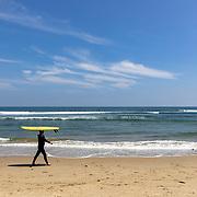 A surfer walks with his board along Surfrider Beach in Malibu, California.
